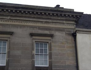 Roof hidden behind decorative stone eaves cornice